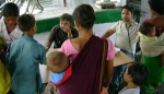 """The   Medical officer of Dhemaji Boat Clinic Dr Hafiz Hafizur Rahman attending to patients on the Dhemaji Boat Clinic """" SB Shahnaz"""". Dr Safiqul Islam(sitting right) looks on"""