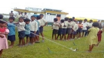 Children from  Mesaki and Lowkiwali Feeder schools in Dibrugarh district queue up for a regular health check up at a camp in Measaki sapori  with Boat Clinic Akha at the backdrop