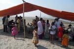 The Lakhimpur Boat Clinic team conducting a health camp on the sandy river bank at Naiboicha sapori.