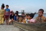 Children wait patiently for their turn at a health camp sitting in a dugout at  Lakhimpur\'s Nawboicha Sapori.